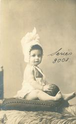 baby in bonnet sitting up on pillow, ball between legs
