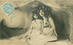 mother & child sit side by side, child left, they both look to front of card