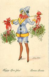 girl carries two large bundles of mistletoe dangling from pole across her shoulders