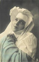 girl faces partly left, looks up, hands clasped in prayer